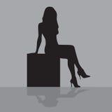 Frau, die auf einem Kasten sitzt lizenzfreies stockbild