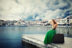 Frau, die auf einem Koffer auf einem Pier spricht am Handy wartet auf das Boot sitzt Lizenzfreie Stockbilder