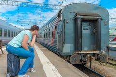 Frau, die auf einem Koffer sitzt und den Zug betrachtet Stockbilder