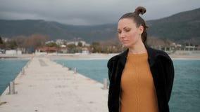 Frau, die auf einem langen Pier in dem Meer im wolkigen Wetter lächelt und steht stock video
