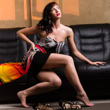 Frau, die auf einem ledernen Sofa sitzt Stockfotografie
