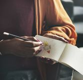 Frau, die auf einem leeren Notizblock notiert stockfoto