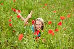 Frau, die auf einem Mohnblumegebiet liegt Stockfotos