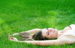 Frau, die auf einem Rasen liegt Stockfotos