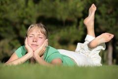 Frau, die auf einem Rasen sich entspannt Lizenzfreies Stockbild