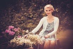 Frau, die auf einem Retro- Fahrrad sitzt Stockfotos