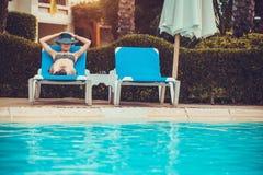 Frau, die auf einem Ruhesessel durch das Pool liegt stockfoto