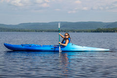 Frau, die auf einem ruhigen See Kayak fährt stockfotografie