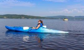 Frau, die auf einem ruhigen See Kayak fährt lizenzfreies stockfoto