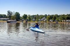 Frau, die auf einem ruhigen See Kayak fährt lizenzfreie stockbilder