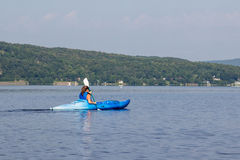 Frau, die auf einem ruhigen See Kayak fährt lizenzfreies stockbild