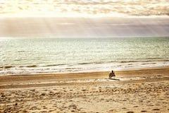 Frau, die auf einem ruhigen Strand sich entspannt Lizenzfreie Stockfotografie