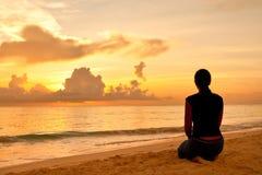 Frau, die auf einem Sandstrand vor Sonnenuntergang sitzt Lizenzfreie Stockbilder