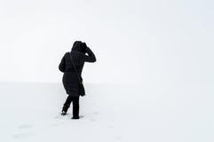 Frau, die auf einem schneebedeckten Gebiet geht Stockbild