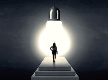 Frau, die auf einem Schritt vor einer enormen Glühlampe steht Stockfotos
