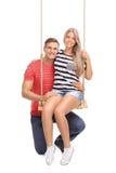 Frau, die auf einem Schwingen sitzt und mit ihrem Freund aufwirft Stockbilder