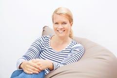 Frau, die auf einem Sitzsack sitzt Stockfotografie
