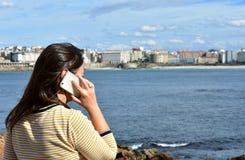 Frau, die auf einem Smartphone in einer Bucht spricht Strand-, Promenaden- und Stadtansicht lizenzfreie stockfotos