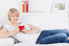 Frau, die auf einem Sofa mit einem roten Becher sich entspannt Stockfotos