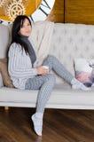 Frau, die auf einem Sofa sitzt lizenzfreie stockfotos