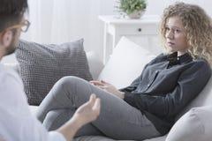 Frau, die auf einem Sofa sitzt Stockfoto