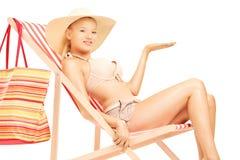Frau, die auf einem Sonnenruhesessel sitzt und mit einer Hand gestikuliert Stockfotografie