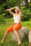 Frau, die auf einem Stein sitzt Lizenzfreie Stockfotos