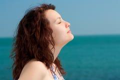 Frau, die auf einem Strand ein Sonnenbad nimmt Lizenzfreie Stockfotos