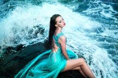Frau, die auf einem Strand mit Felsen aufwirft Stockfoto
