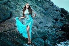 Frau, die auf einem Strand mit Felsen aufwirft Lizenzfreie Stockfotografie
