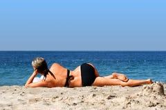 Frau, die auf einem Strand sich entspannt stockfoto