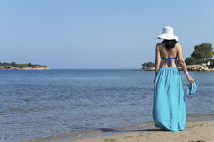 Frau, die auf einem Strand steht und Paare Pantoffel hält Lizenzfreie Stockfotografie