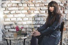 Frau, die auf einem Stuhl in der Kaffeestube sitzt Lizenzfreie Stockfotografie