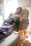 Frau, die auf einem Stuhl mit ihrem Kind stillsteht Stockfoto