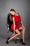 Frau, die auf einem Stuhl sitzt Lizenzfreie Stockfotos