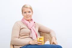 Frau, die auf einem Stuhl sitzt Stockbild