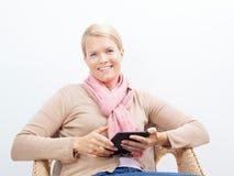 Frau, die auf einem Stuhl sitzt Lizenzfreies Stockbild
