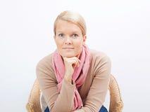 Frau, die auf einem Stuhl sitzt Lizenzfreie Stockbilder