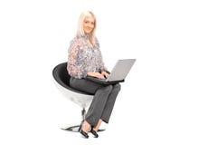 Frau, die auf einem Stuhl sitzt und an einem Laptop arbeitet Lizenzfreie Stockbilder