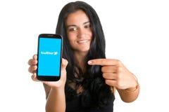 Frau, die auf einen Handy zeigt Lizenzfreies Stockbild