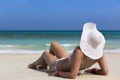 Frau, die auf einen Strand legt Lizenzfreie Stockbilder