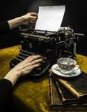 Frau, die auf einer alten Schreibmaschine schreibt Lizenzfreie Stockfotos