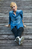 Frau, die auf einer Anlegestelle oder einer Brücke sitzt Lizenzfreies Stockfoto