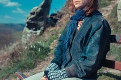 Frau, die auf einer Bank in den Bergen sich entspannt Lizenzfreie Stockfotografie