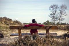 Frau, die auf einer Bank in der Natur sitzt stockbild