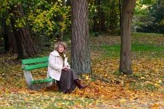 Frau, die auf einer Bank im Park sitzt stockbild