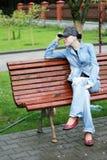 Frau, die auf einer Bank im Park sitzt Lizenzfreies Stockbild