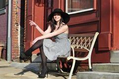 Frau, die auf einer Bank sitzt Lizenzfreie Stockbilder