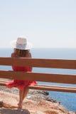 Frau, die auf einer Bank sitzt stockbild