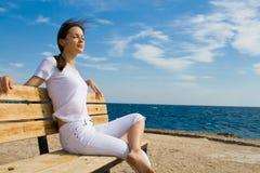 Frau, die auf einer Bank sitzt Stockfotos
